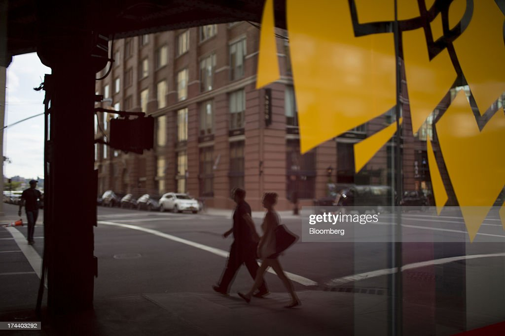 A couple walking down the street is reflected in the window of a store in New York, U.S., on Wednesday, July 24, 2013. The U.S. Conference Board is scheduled to release consumer confidence figures on July 30. Photographer: Scott Eells/Bloomberg via Getty Images