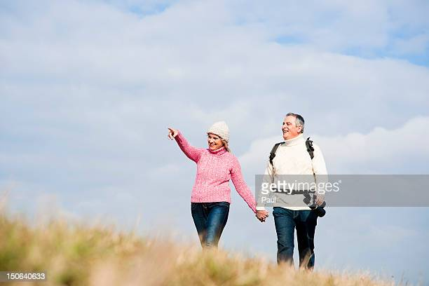 Couple walking hand in hand in meadow