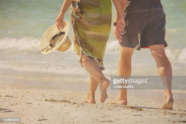 Couple walking hand in hand on beach