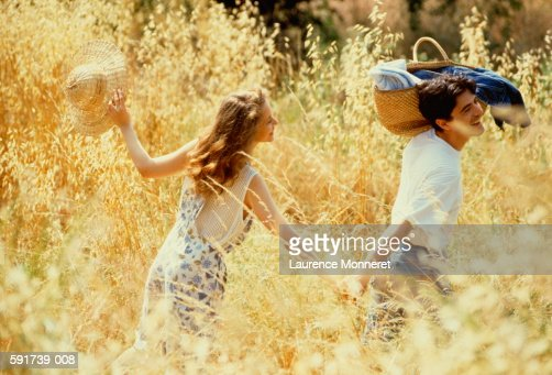 Couple walking hand in hand through field,man with basket on shoulder : Stock Photo