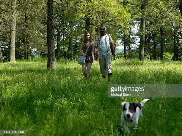 Couple walking hand in hand through park with dog, smiling, portrait