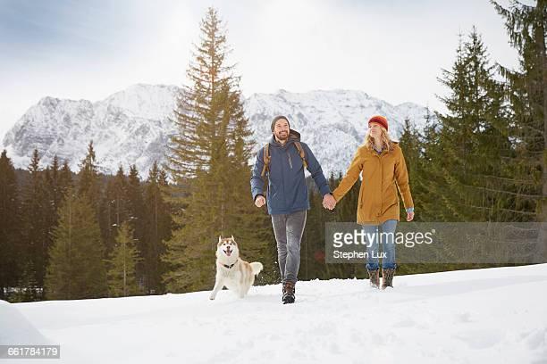 Couple walking husky in snow covered landscape, Elmau, Bavaria, Germany