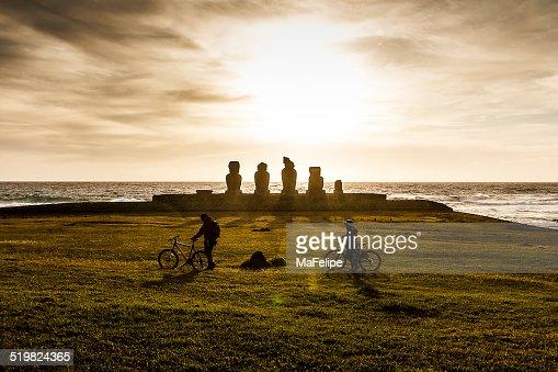 Couple walking in Ahu Tahai Moai Statues at Sunset