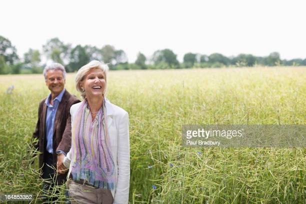 Casal caminhar no campo de alto Relva