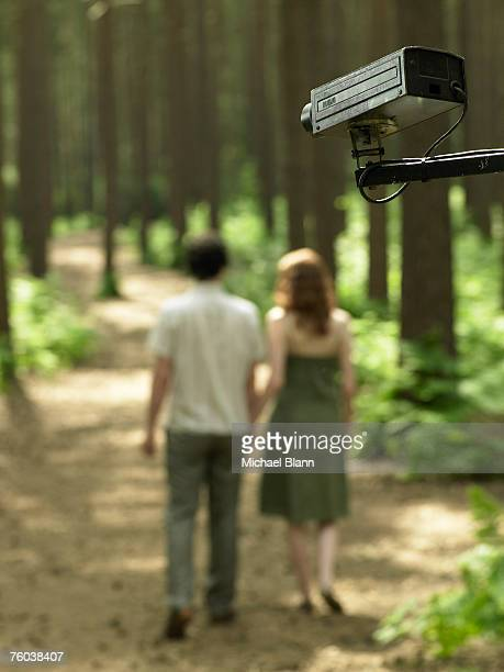 Couple walking in forest, rear view, focus on surveillance camera in foreground