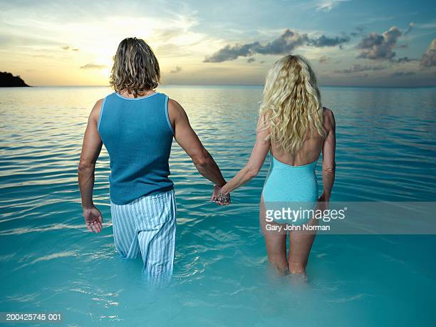 Couple walking in ocean, holding hands, rear view