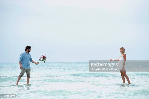 Couple walking in sea towards each other, man holding out bouquet