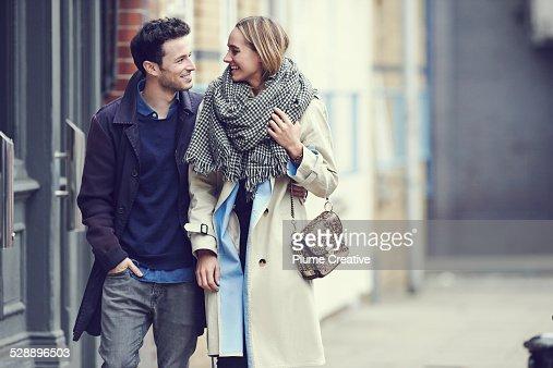Couple walking in street arm in arm