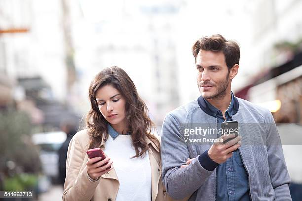 Couple walking in the street watching their phones
