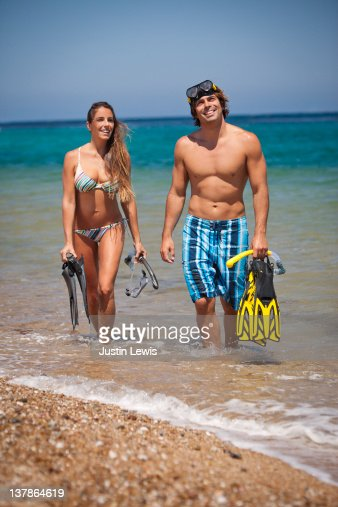 A couple walking in the water with snorkeling gear : Stock Photo