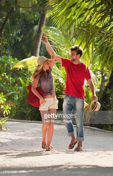 Couple marchant dans le centre de villégiature tropical