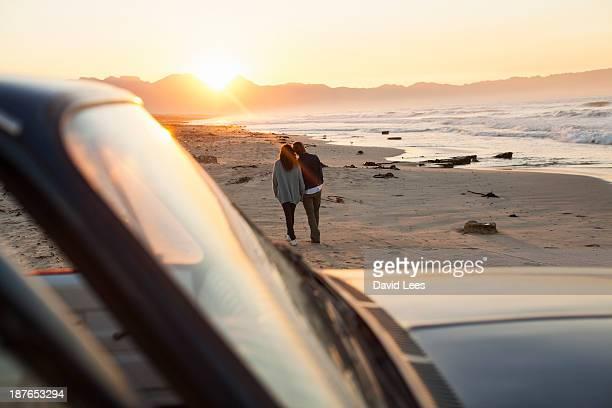 Couple walking on beach by truck
