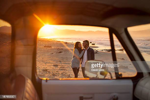 Couple walking on beach by truck
