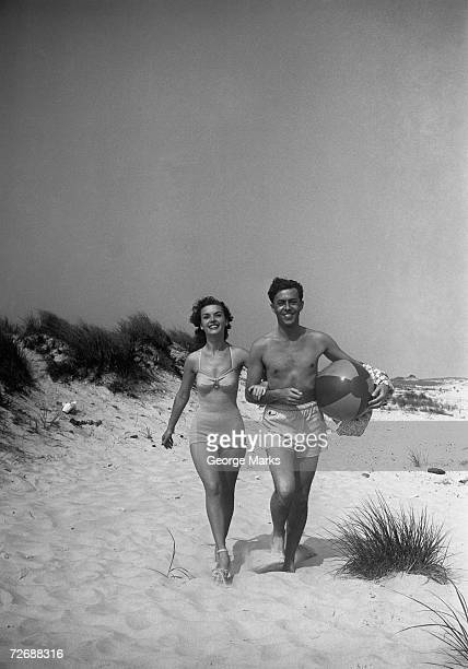 Couple walking on beach, man carrying ball, (B&W)