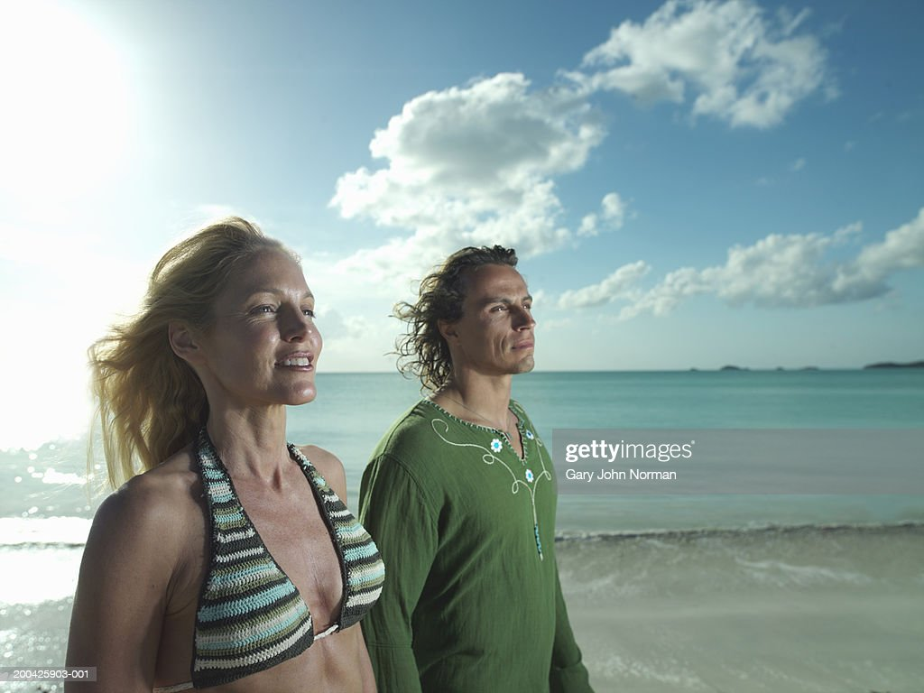 Couple walking on beach, side view