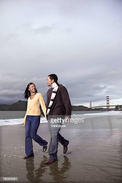 Couple walking on beach with Golden Gate Bridge behind