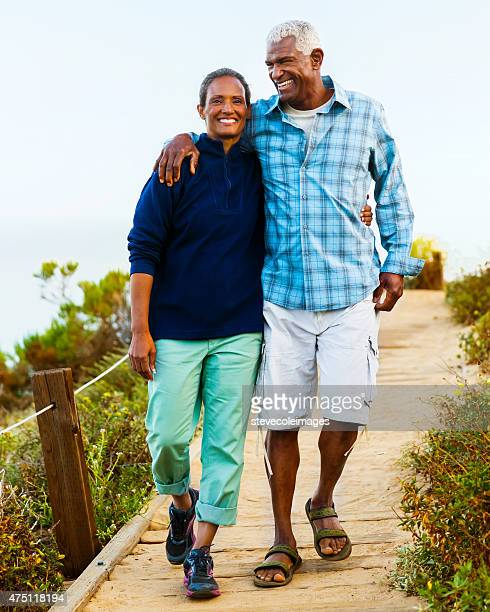 Couple walking on boardwalk.