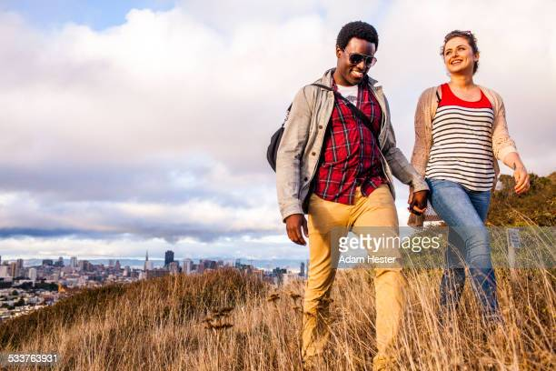 Couple walking on grassy hill overlooking cityscape