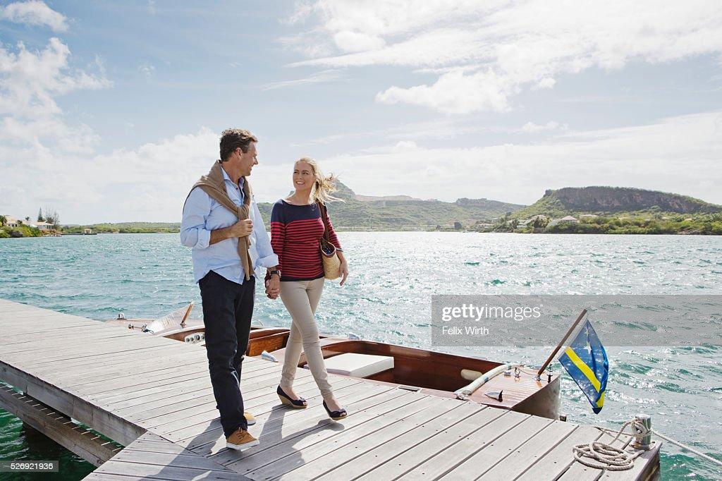 Couple walking on jetty : Stock Photo