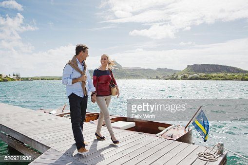 Couple walking on jetty : Stock Photo