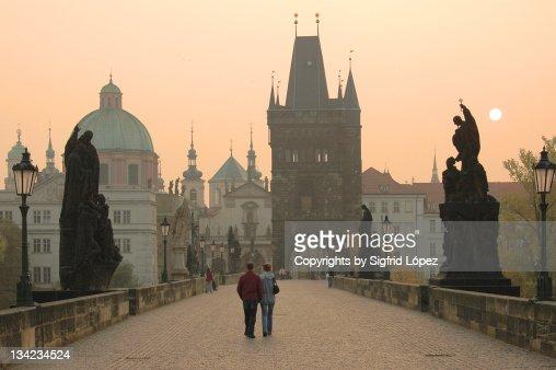 Couple walking on Prague's Charles' bridge