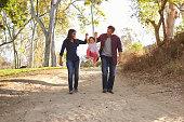 Couple walking on rural path lifting daughter, full length