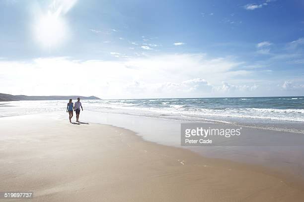 Couple walking on the beach holding hands