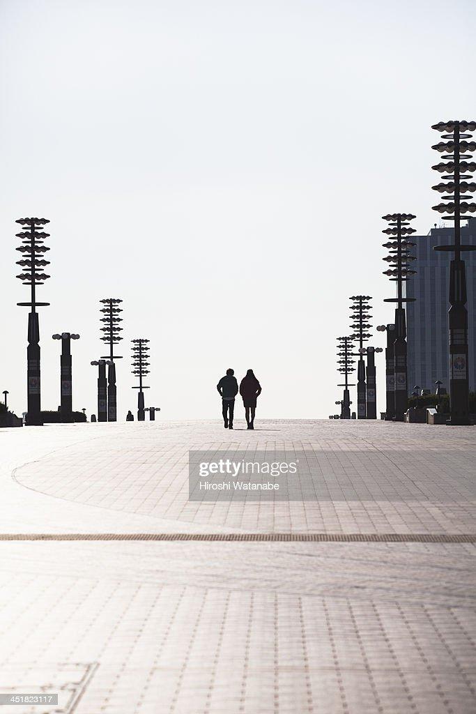Couple walking on the pavement : Stock Photo