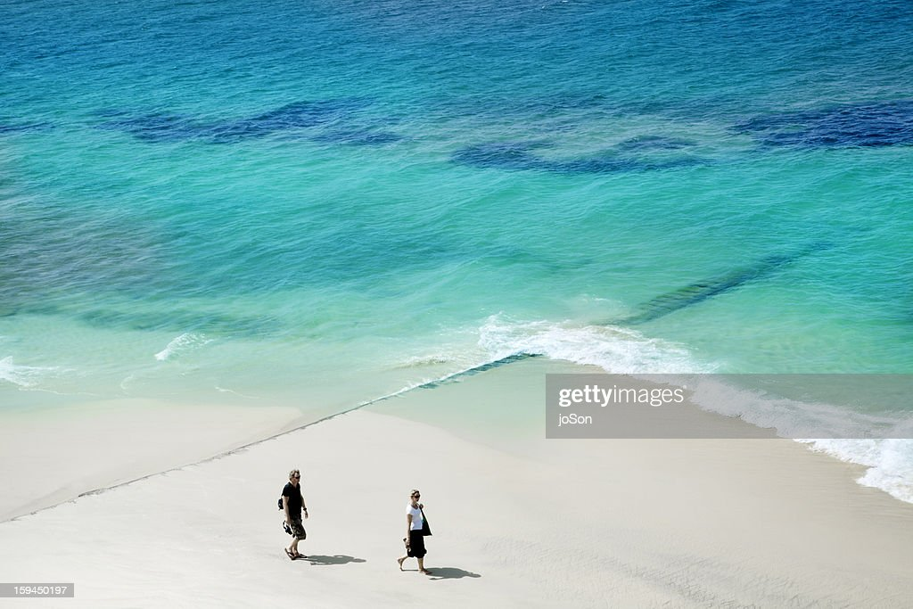 Couple walking on while sand beach : Stock Photo