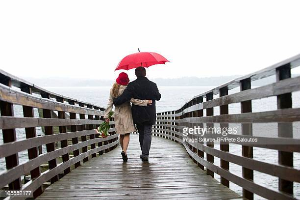 Couple walking on wooden pier in rain
