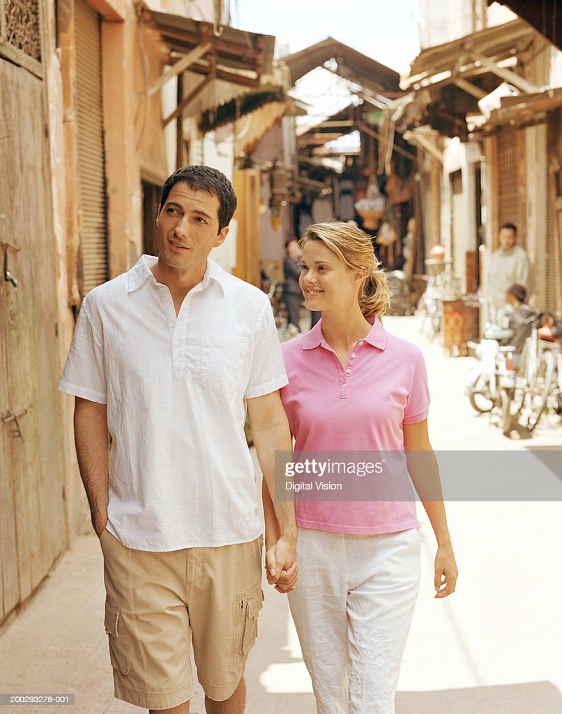 Couple walking outdoors, holding hands, smiling