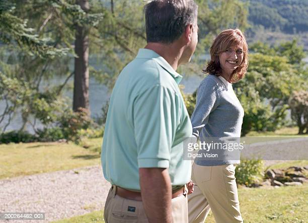 Couple walking outdoors holding hands, woman smiling at man