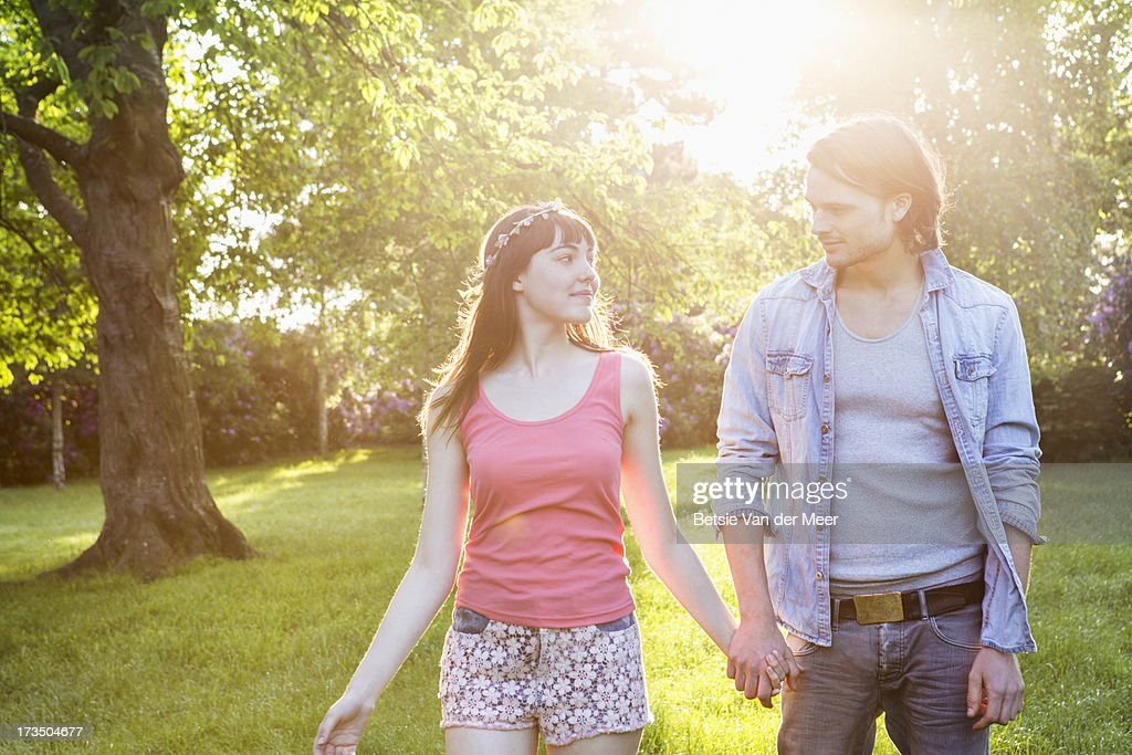 Couple walking outdoors in sunshine. : Stock Photo