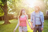 Couple walking outdoors in sunshine.
