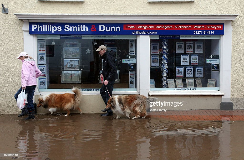 A couple walking their dogs passes receding flood water in the centre of the Devonshire town of Braunton that was flooded yesterday on December 23, 2012 near Barnstaple, England. Flooding has brought further disruption to many parts of the UK including the South West of England that was particularly badly hit. The Met Office are warning of further bands of heavy rain tonight and the Environment Agency has issued 100s of flood warnings for England including one severe warning for Cornwall.