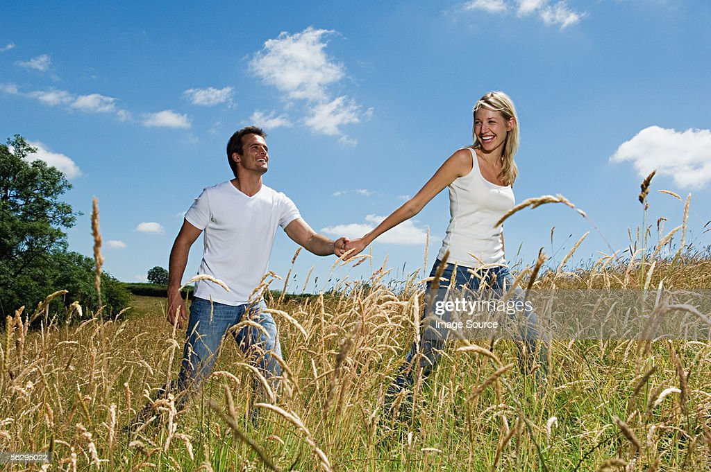 Couple walking through field : Stock Photo