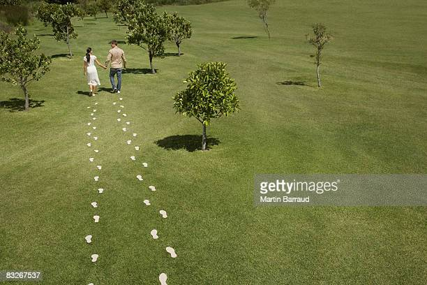 Couple walking through field trailing footprints