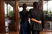 Couple walking through hotel door, rear view