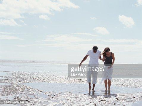 Couple walking through shallow pool on beach : Stock Photo