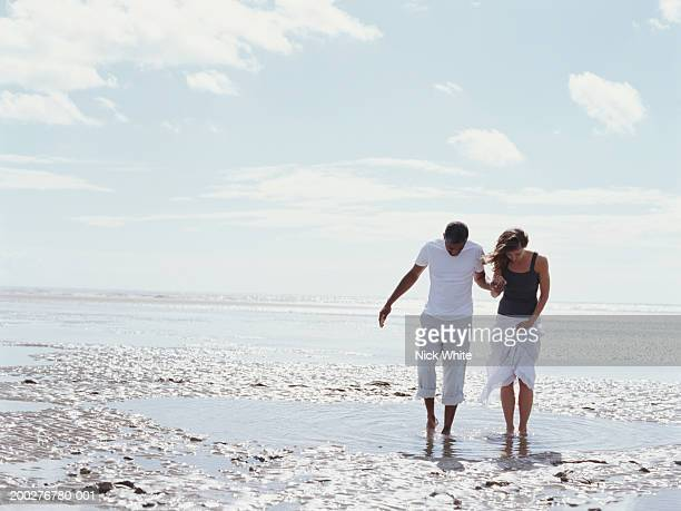 Couple walking through shallow pool on beach
