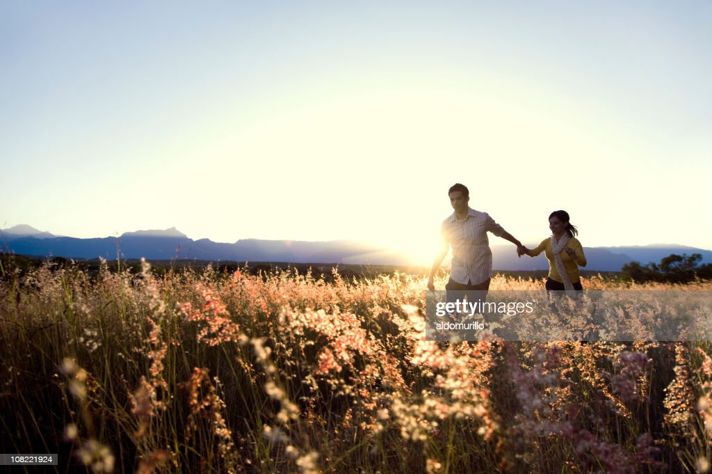 Couple Walking Through Tall Grass Field at Sunset : Stock Photo