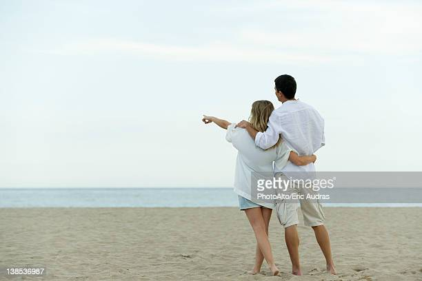 Couple walking together at the beach, woman pointing at sea