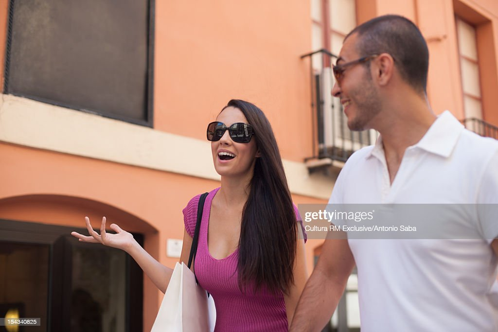 Couple walking together on city street : Stock Photo