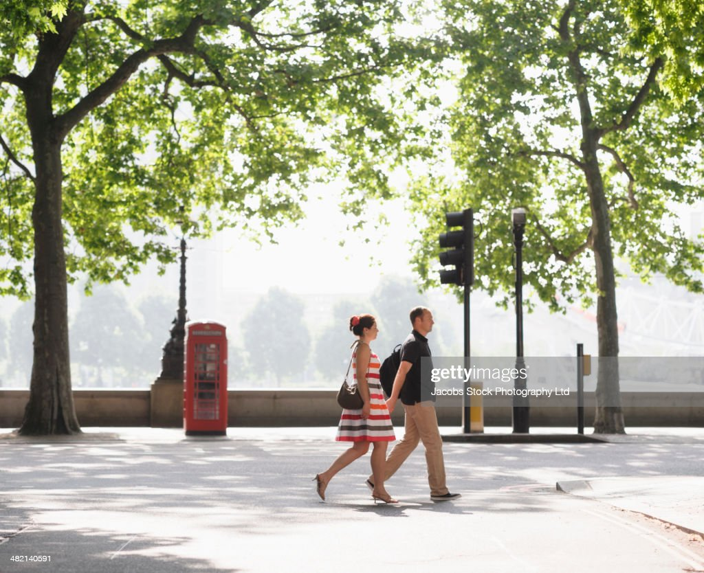 Couple walking together on urban street, London, United Kingdom