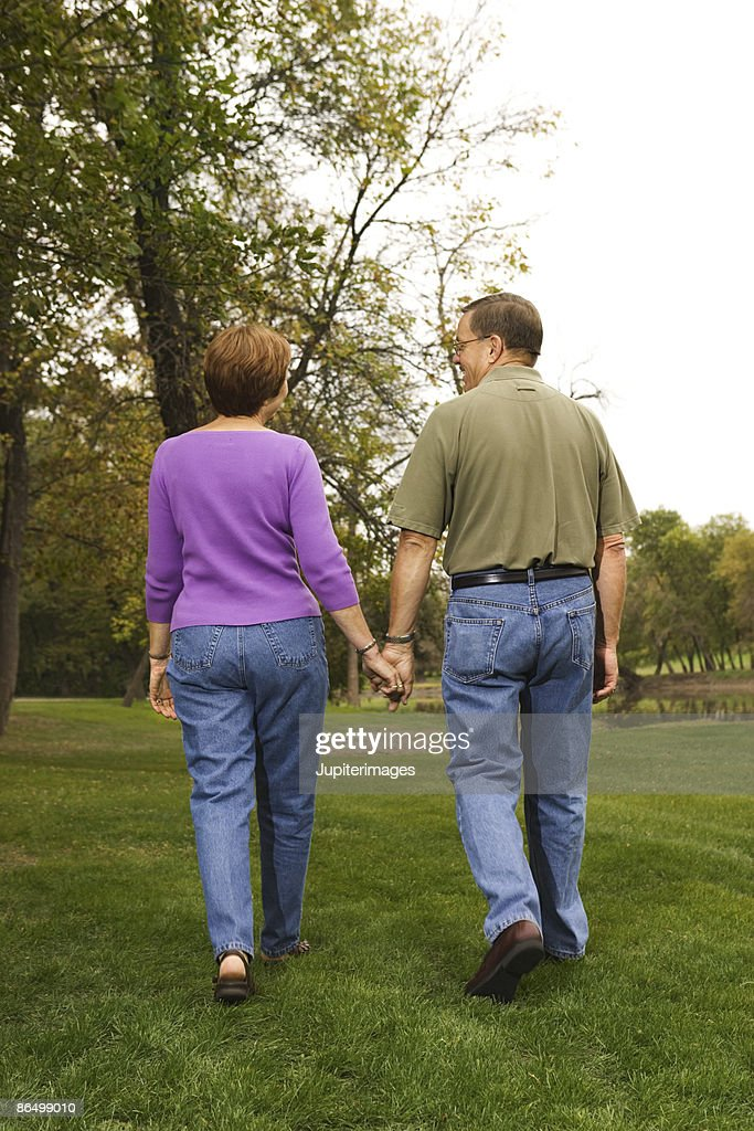Couple walking together outdoors : Stock Photo