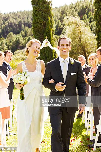 Couple Walking Together With Guests Clapping During Ceremony