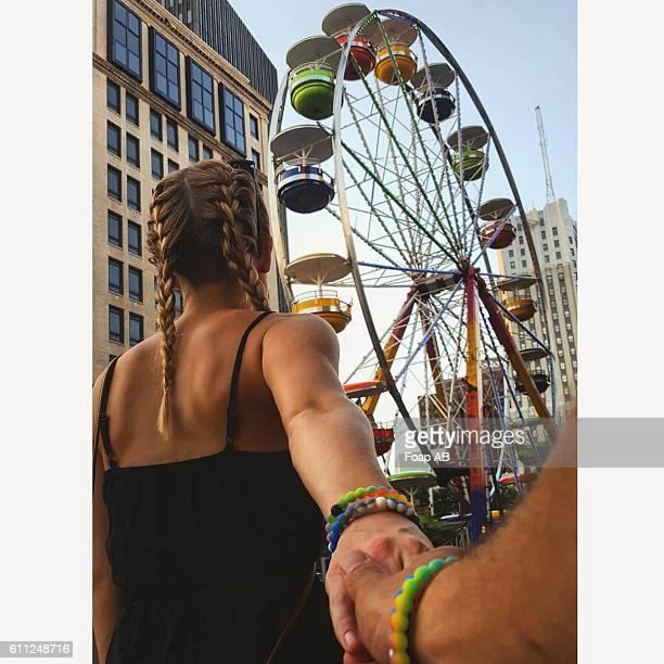 Couple walking towards ferris wheel