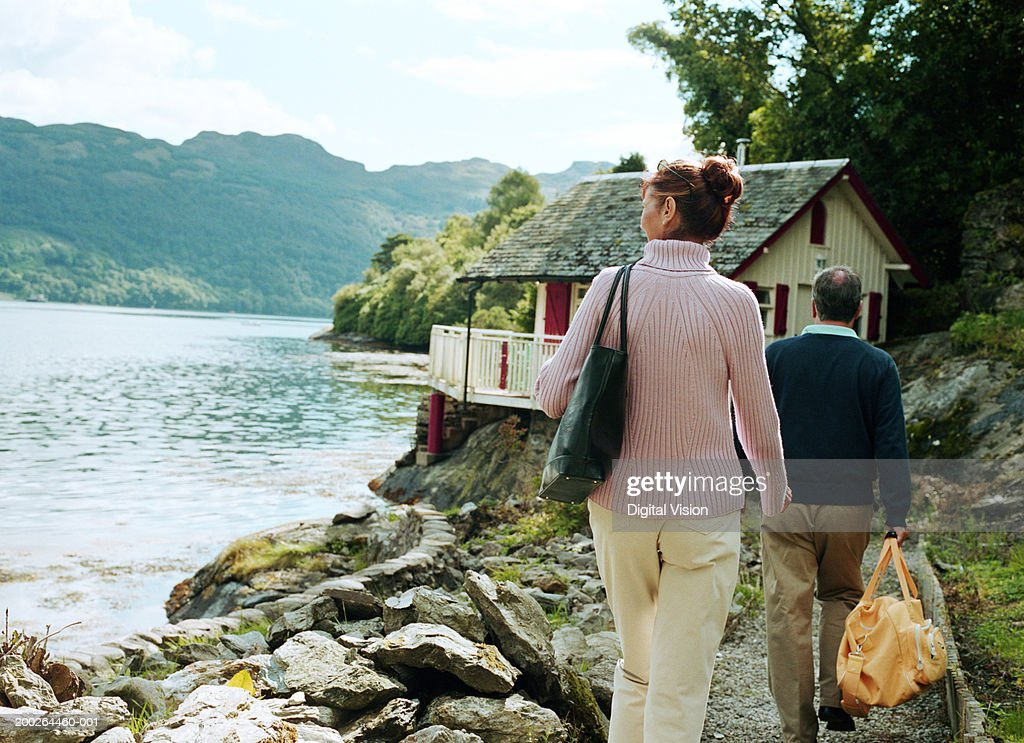 Couple walking towards house by water, rear view