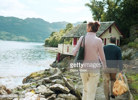 Couple walking towards house by water, rear view : Bildbanksbilder