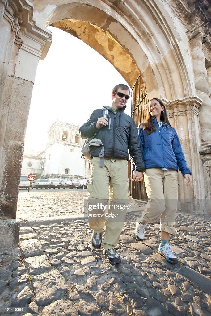 Couple walking under arch on cobblestone street. : Stock Photo